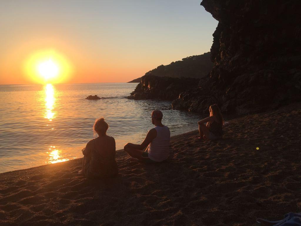 3 mensen op het strand bij zonsondergang in Yoga houding